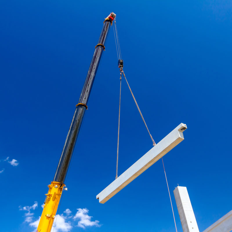 Mobile crane is operating with a huge concrete joist that hangs on chain.